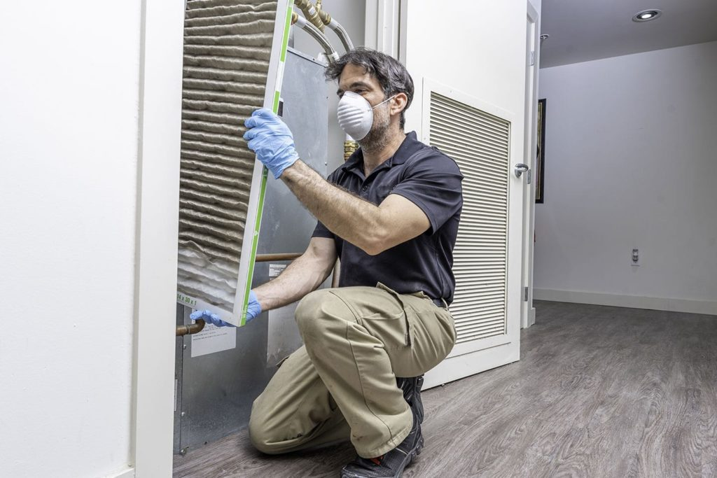Professional changing air filter in HVAC unit in Belleville, Illinois