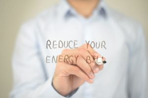 """A young man writing """"Reduce Your Energy Bill"""" on a clear board with a marker in Belleville, Illinois."""