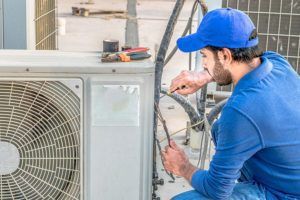 A professional air conditioning repair technician working on an A/C unit that will not produce cool air in Belleville, Illinois