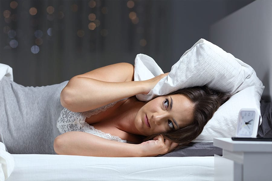 Woman hearing a loud noise from her air conditioning unit and covering her ears with a pillow in Belleville, Illinois